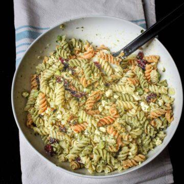 pesto pasta salad in large white bowl on blue striped cloth.