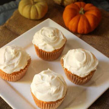 square white plate holding four frosted cupcakes next to pile of mini pumpkins.