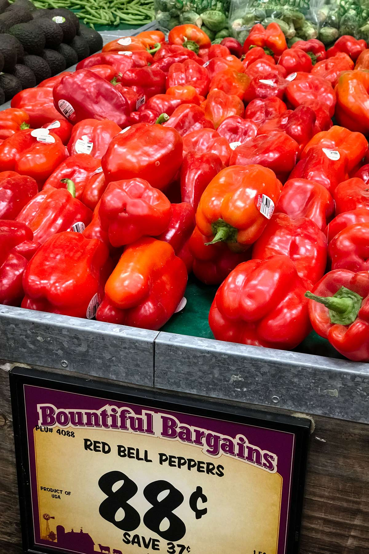 red peppers on display at the grocery store for 88 cents each.