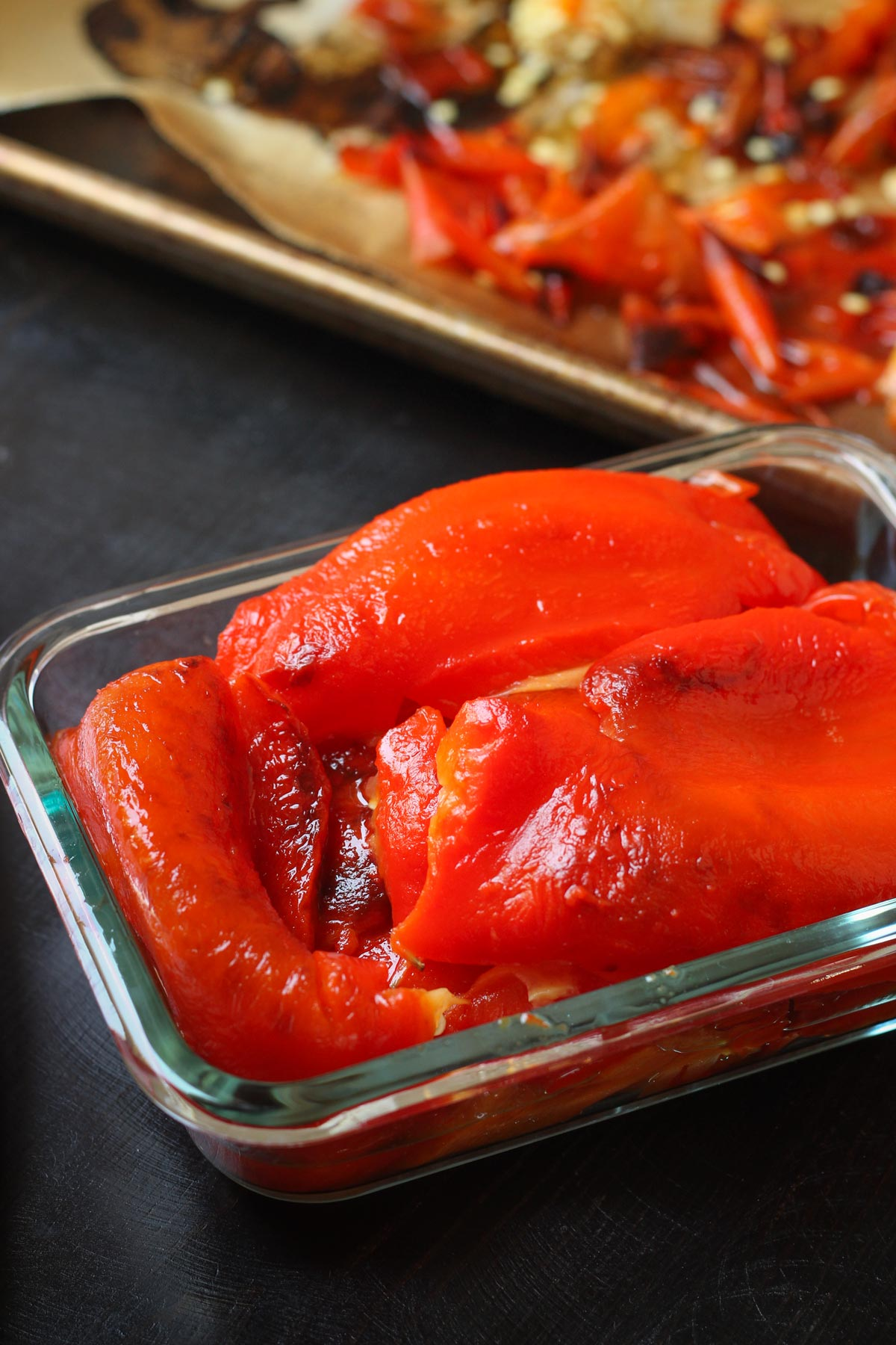 peeled and roasted red peppers in a small glass storage container.