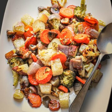 close up of roast vegetables on white platter with serving spoon.