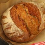 baked sourdough rye boule on paper in dutch oven.
