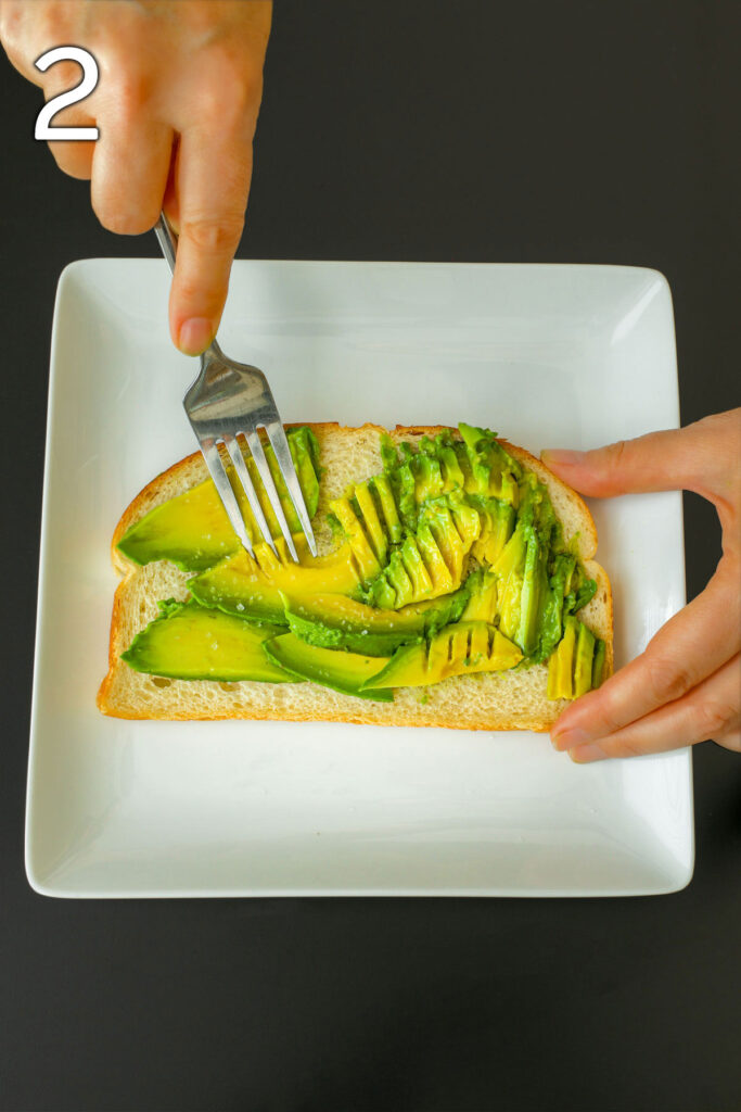 using a fork to mash avocado slices onto the toast.