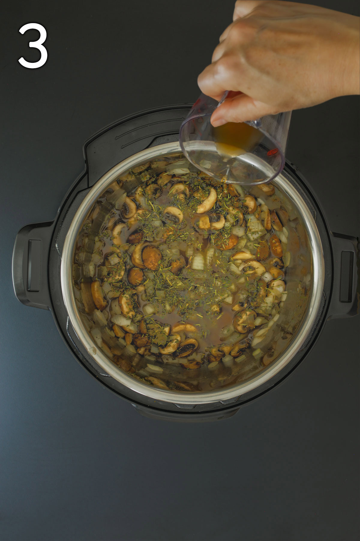 adding beef broth to vegetables and herbs in pot.
