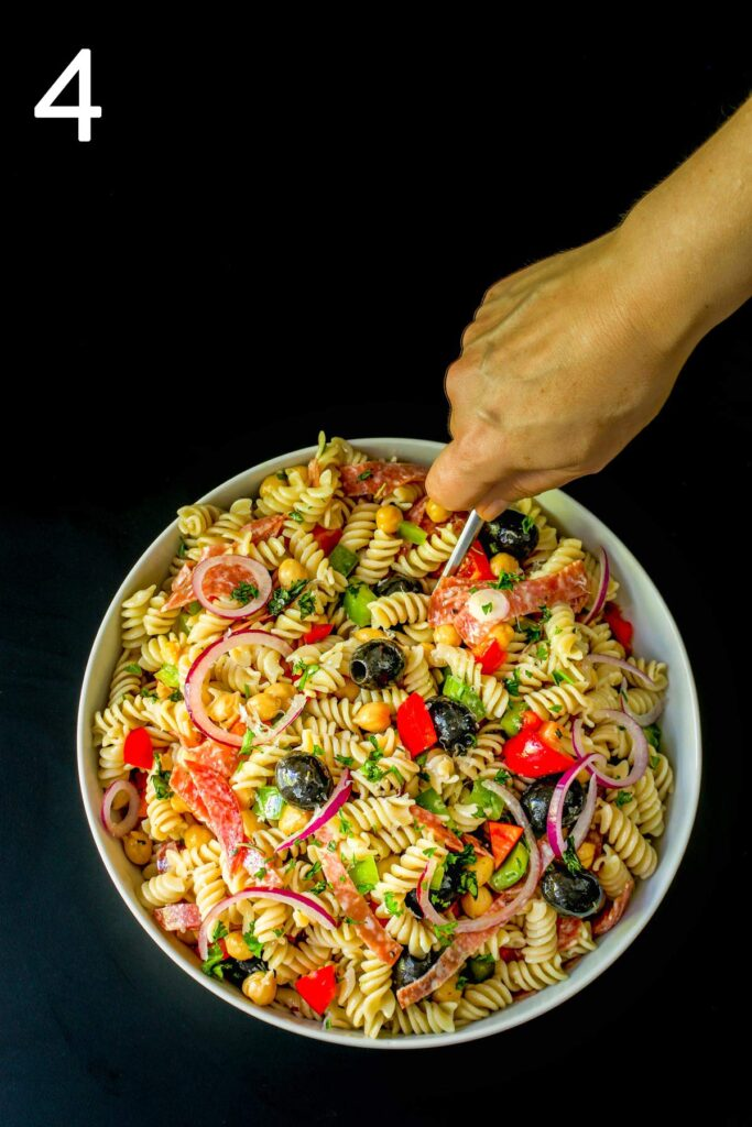 stirring the elements of the pasta salad together.