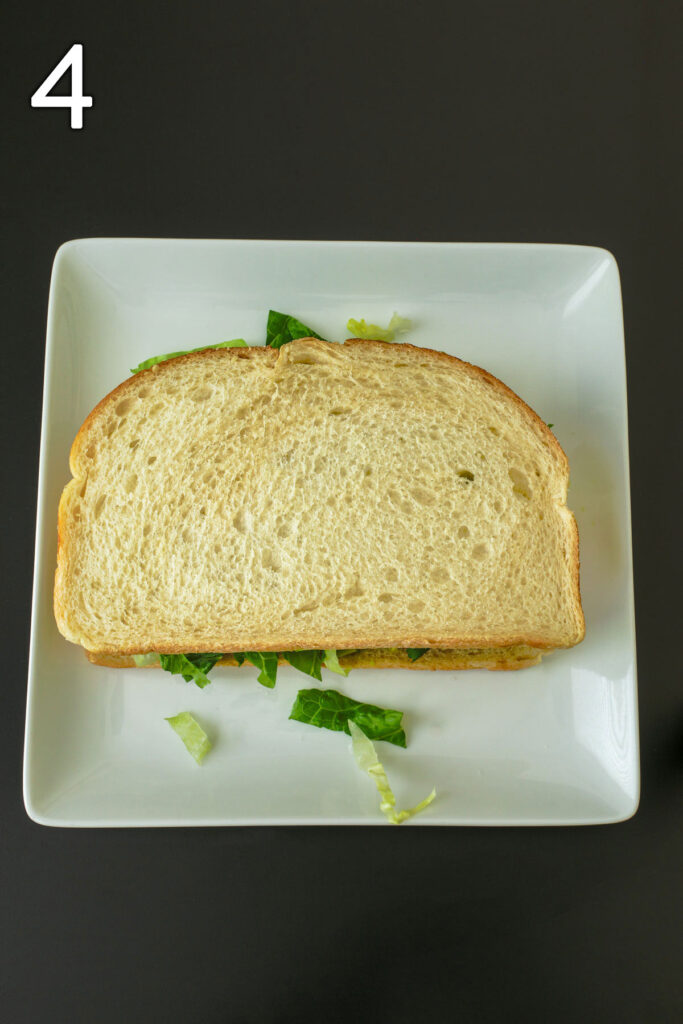 sandwich on plate fully assembled and ready to eat.