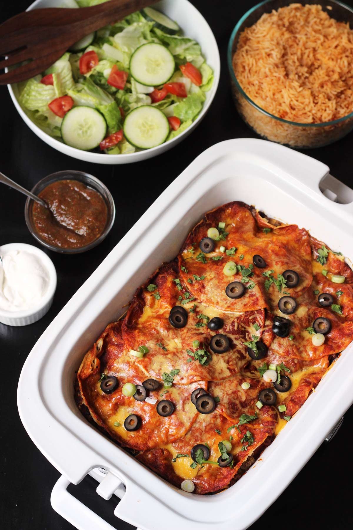 table set with casserole crock pot of enchiladas with toppings, rice, and salad.