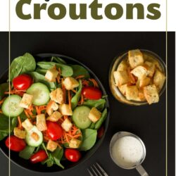 spinach salad topped with croutons next to jar of croutons, small dish of dressing, and a fork, all on a black table top.