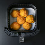 six pumpkin biscuits on parchment paper in air fryer basket.