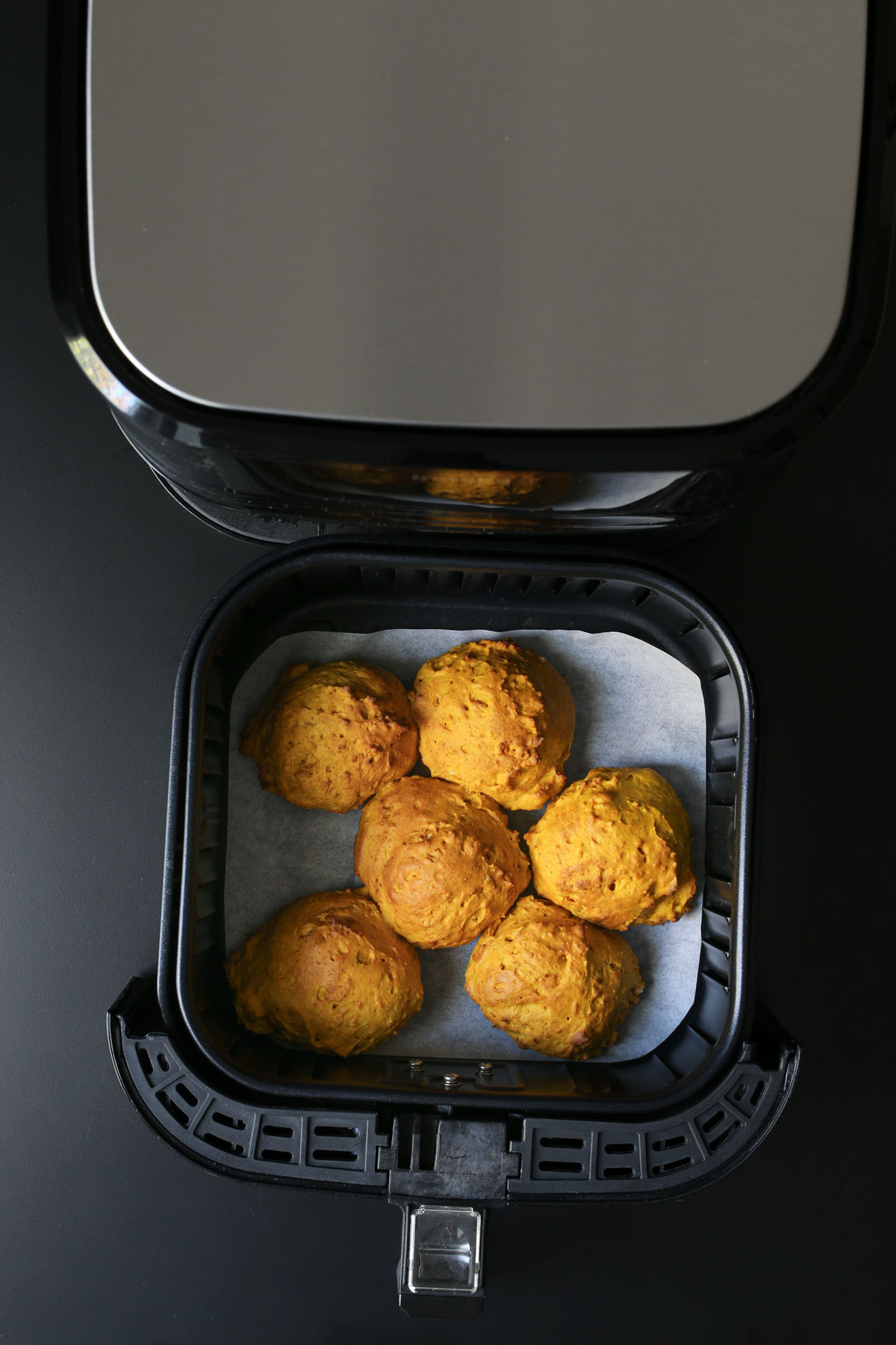 baked biscuits in air fryer basket.