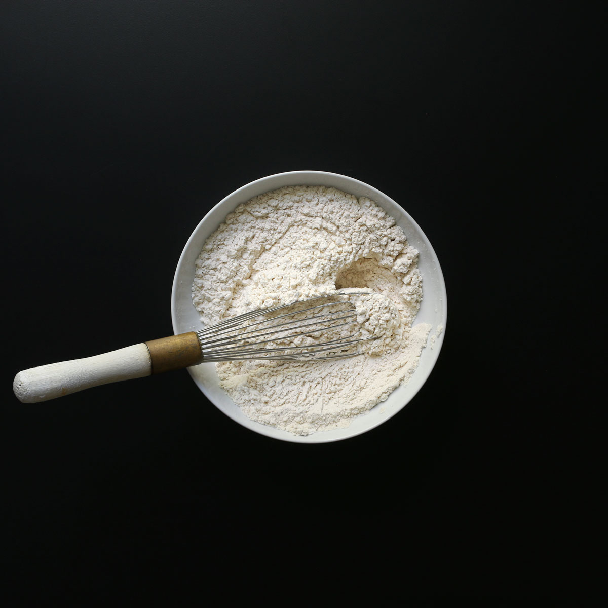 dry ingredients whisked together in white mixing bowl.
