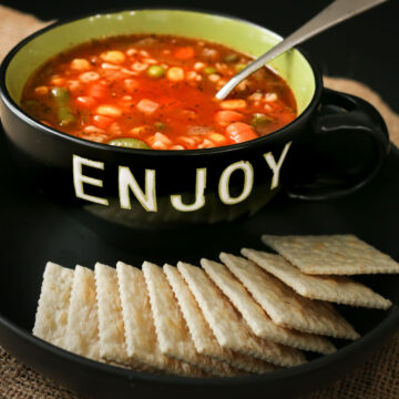 alphabet soup in black bowl marked ENJOY with plate of saltines.