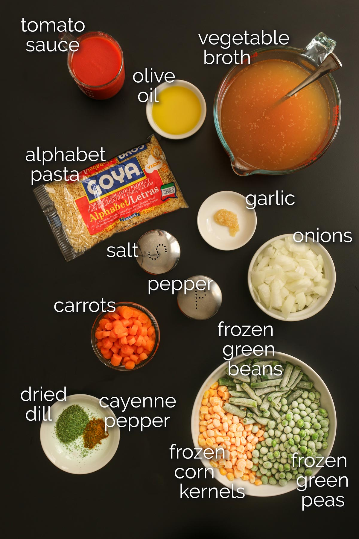 ingredients for vegan soup with alphabet noodles laid out on black table top.