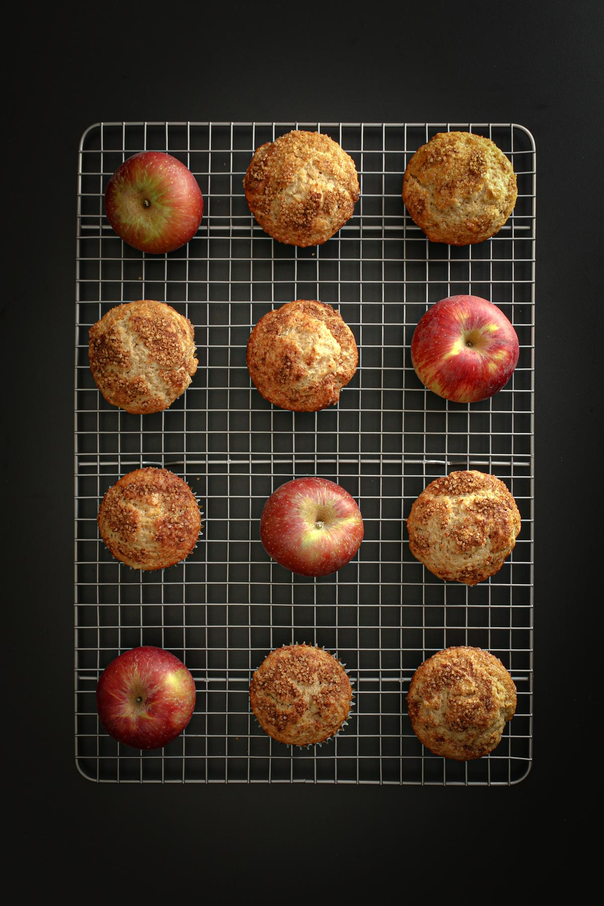 an array of red apples and apple muffins cooling on a steel wire rack on a black table top.