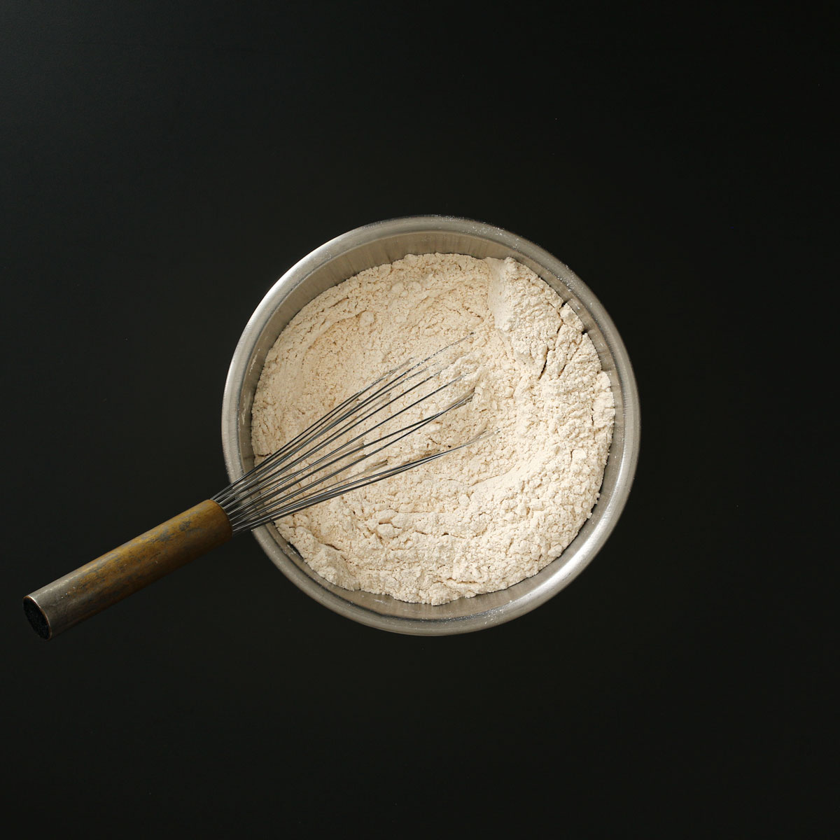 metal whisk submerged into dry ingredients in steel bowl.
