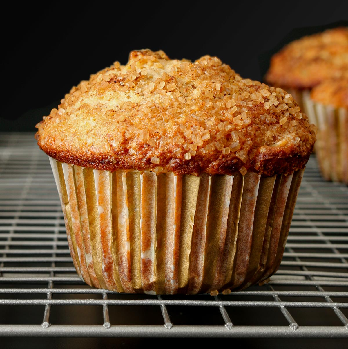 close up of apple cinnamon muffin in striped paper cooling on silver wire rack on black table.