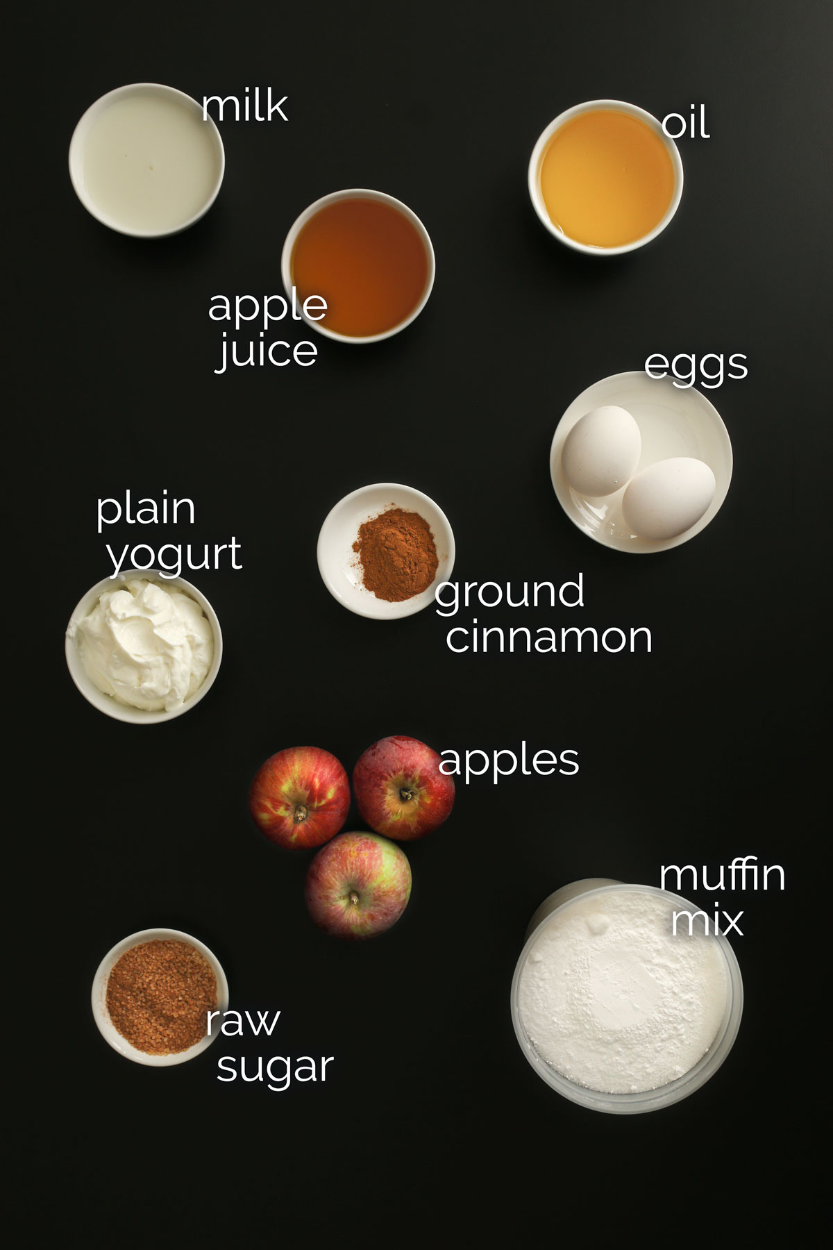 ingredients for apple cinnamon muffins measured out into small dishes and laid out on a black table top.