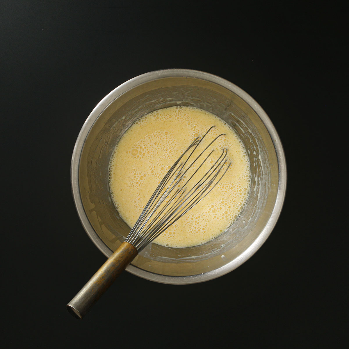 whisk submerged into wet ingredients that have been mixed together in metal bowl.
