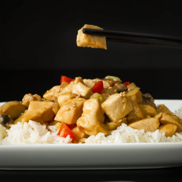 piece of chicken held in black chopsticks over square white plate of chicken stir fry on bed of rice.