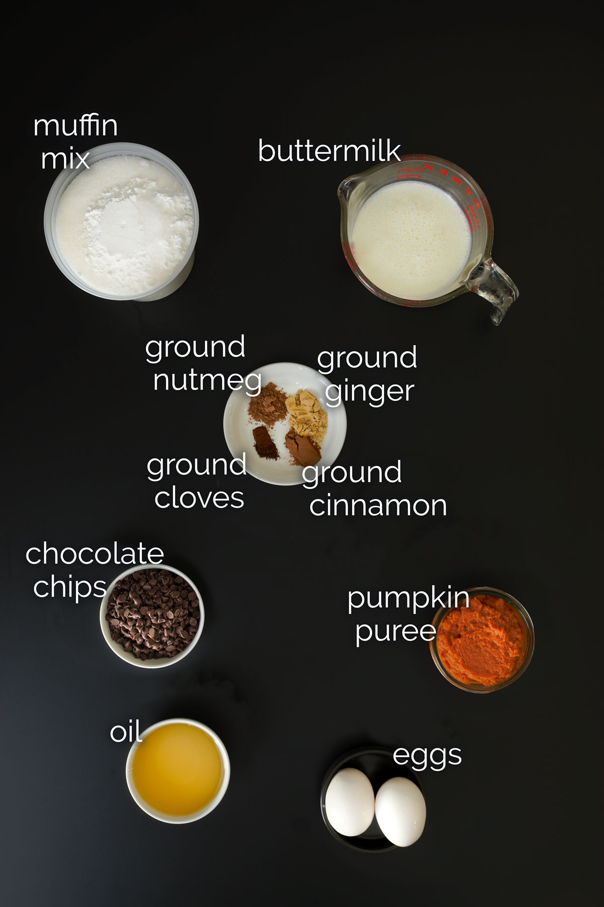 ingredients for pumpkin muffins laid out on black table top.