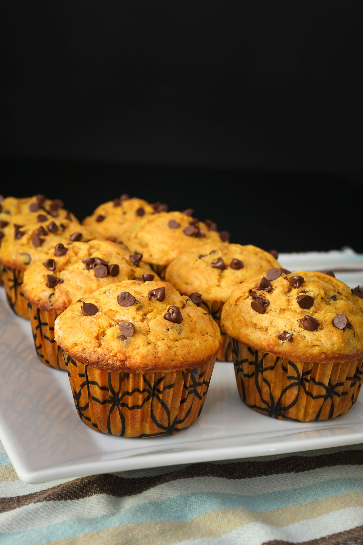 pumpkin muffins lined up on a white serving tray on a blue striped cloth.