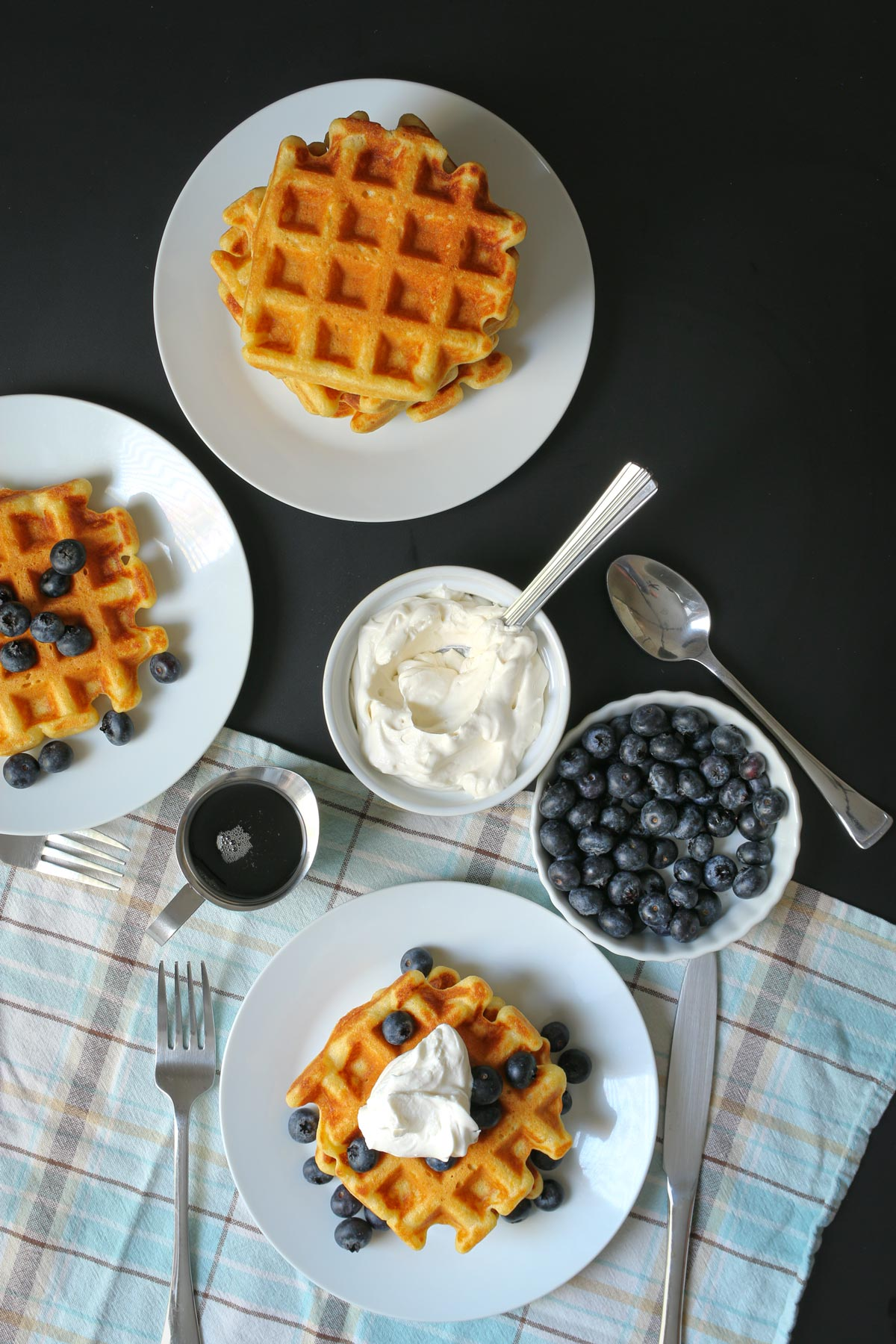 breakfast table set with waffles, syrup, whipped cream, and blueberries.