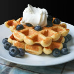 close-up of waffles stacked on a plate topped with whipped cream and blueberries.