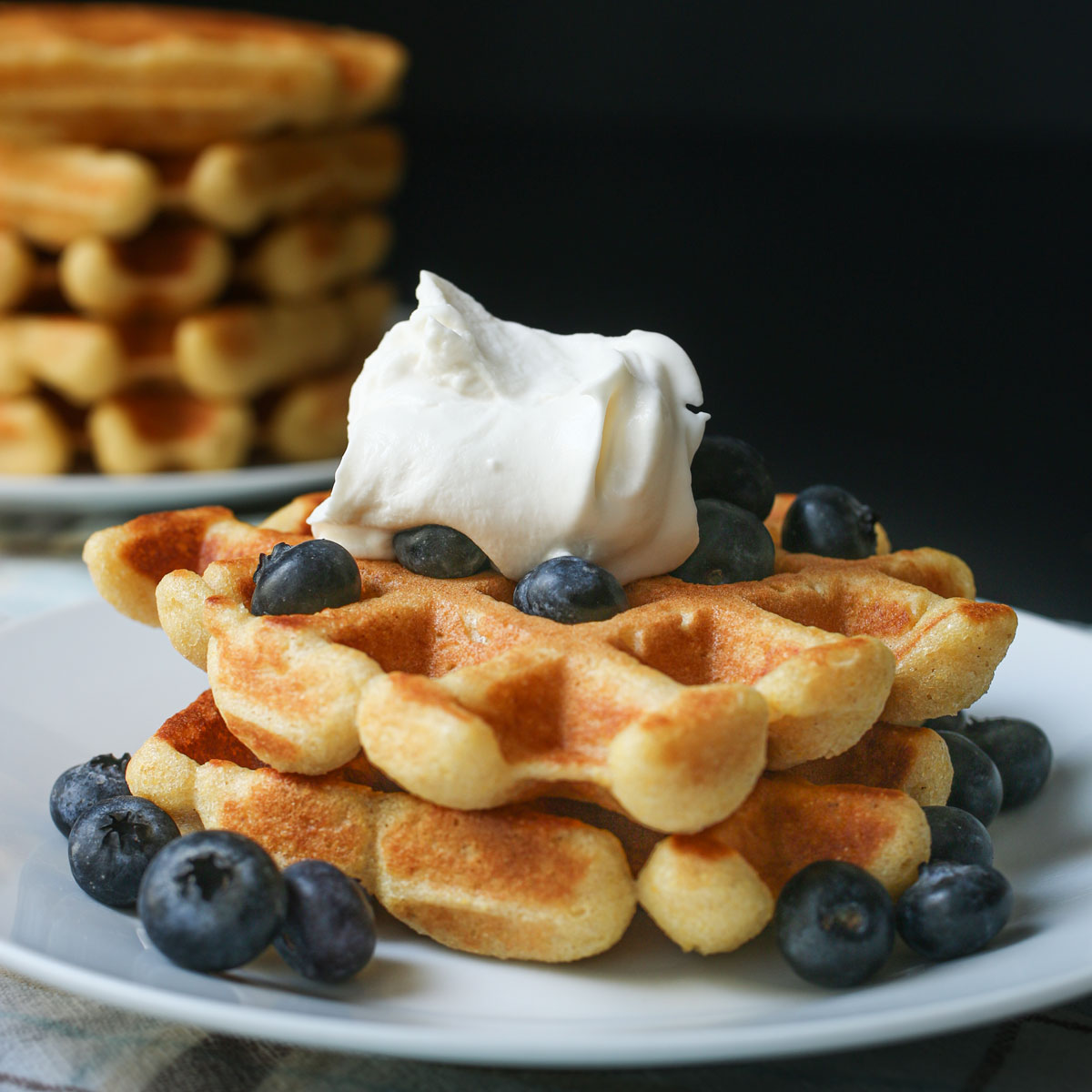 pair of cornbread waffles topped with blueberries and whipped cream on a white plate near a stack of waffles.