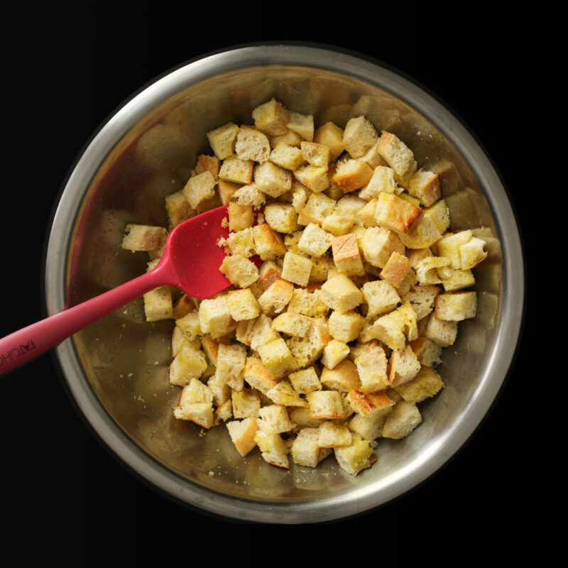 stirring bread cubes and oil together with red spatula.