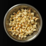large metal bowl filled with bread cubes on black table.