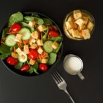 croutons on spinach salad as well as in small jar next to salad bowl, with dressing and fork on table nearby.