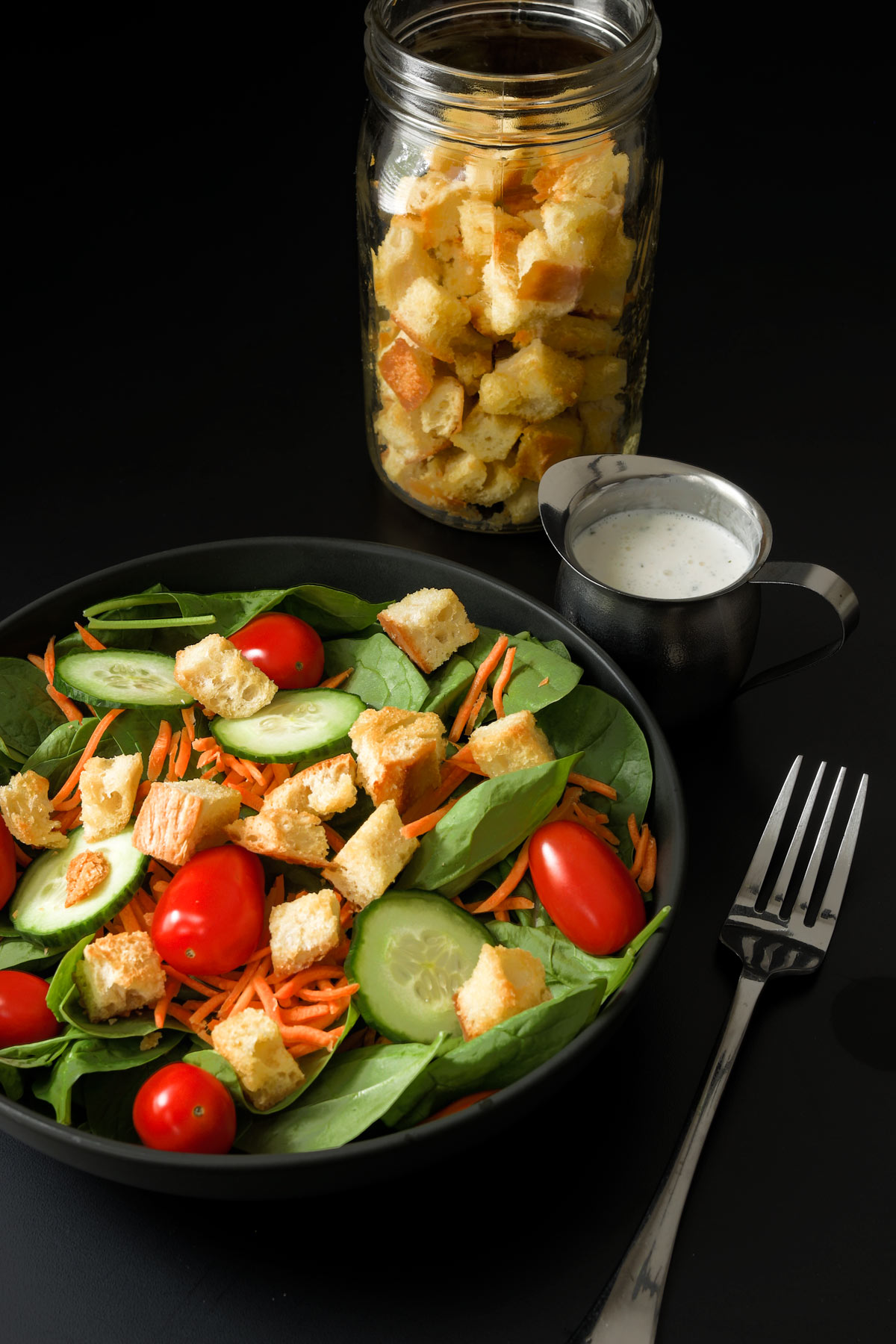 spinach salad in black bowl topped with croutons near a mason jar of croutons, a fork, and a dish of ranch dressing.