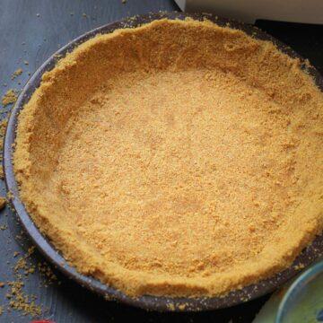 graham cracker crust in brown pie plate on work table.