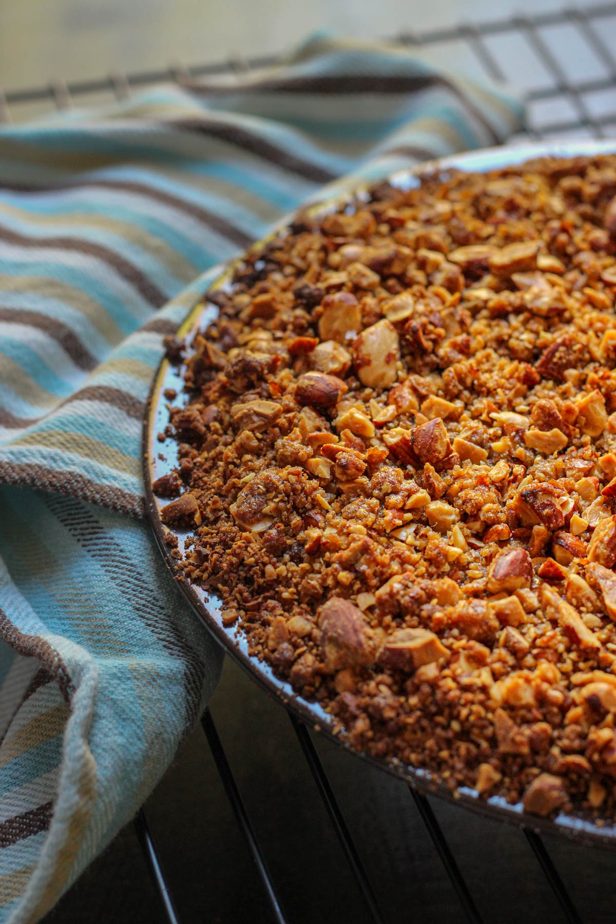 streusel topped pumpkin pie in a graham cracker crust set on a blue and brown striped cloth.