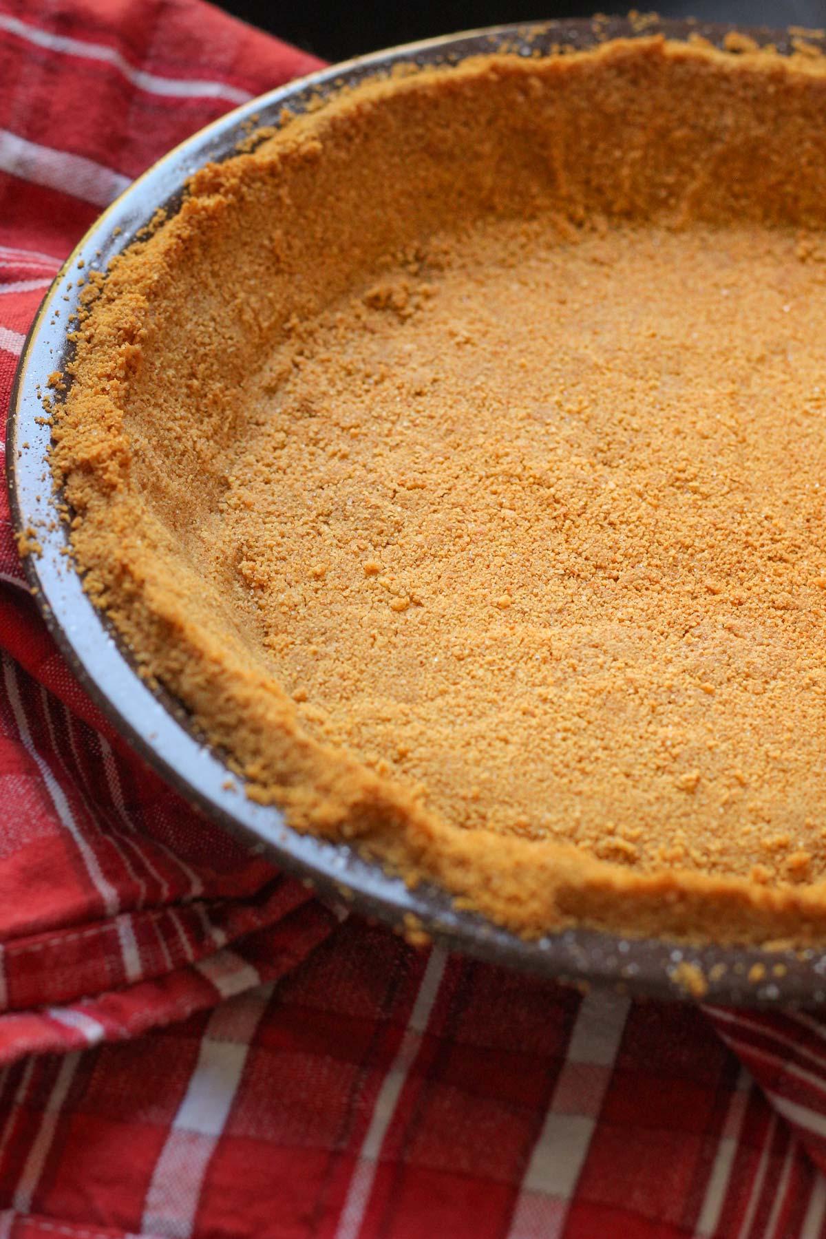 graham cracker crust in brown pie plate on red plaid towel.