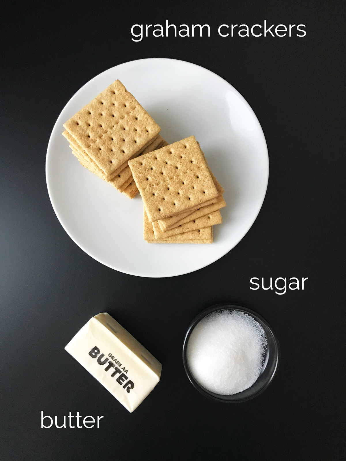 graham crackers, sugar, and butter laid out on a black table top.