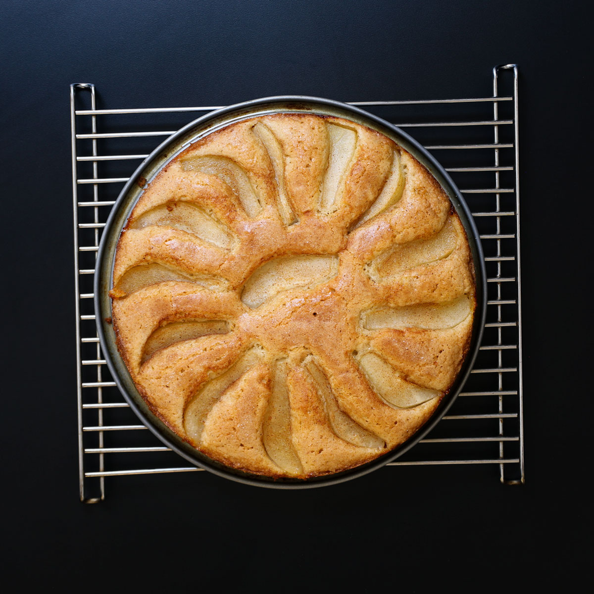 baked pear cake cooling on rack.