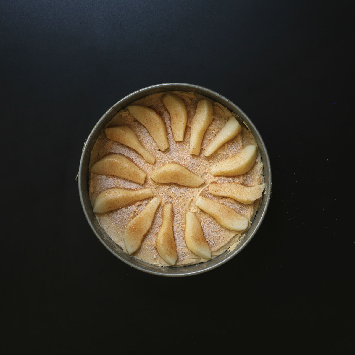 assembled pear cake in pan unbaked.