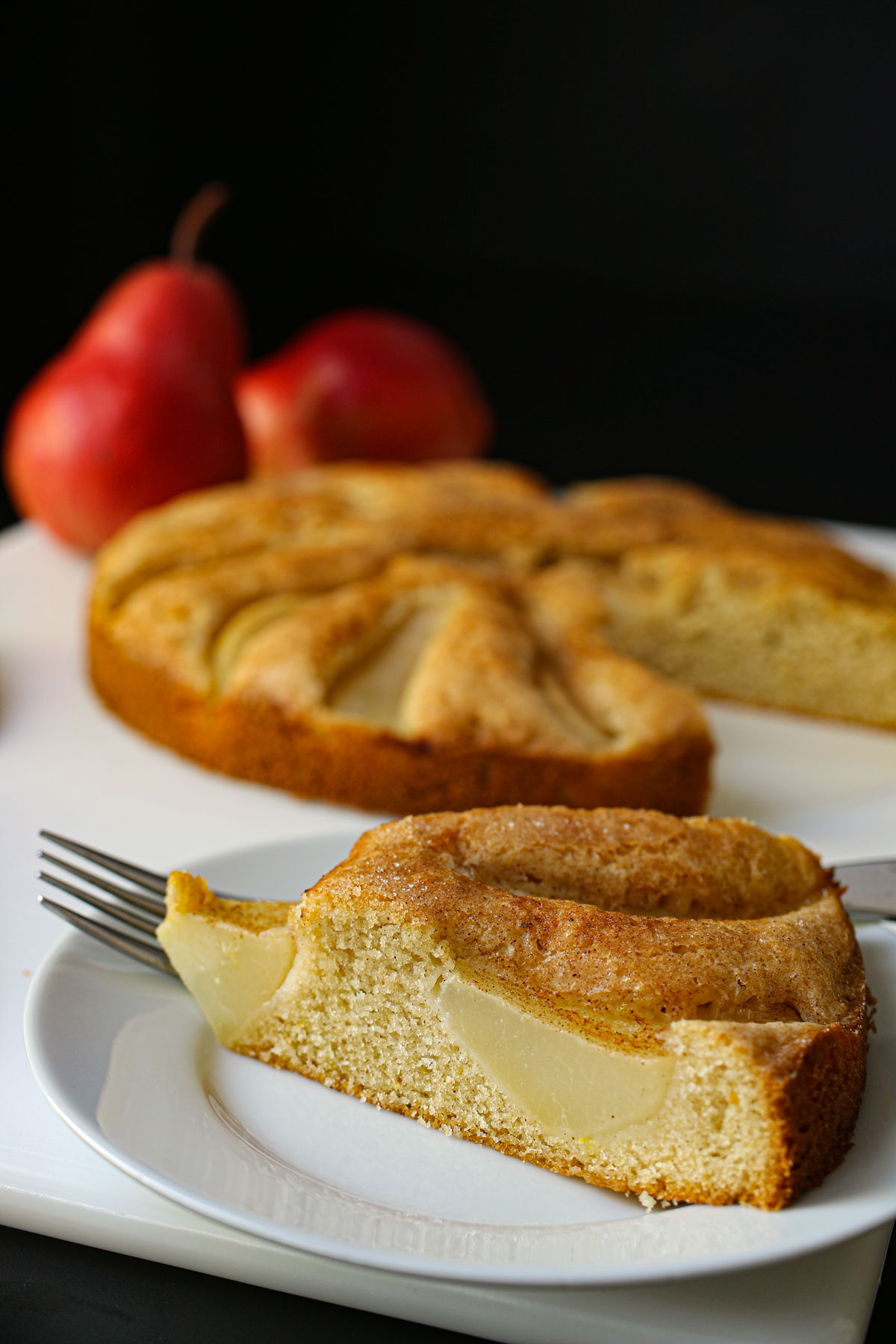 pear cake served on dessert plate next to cake platter and two red pears.