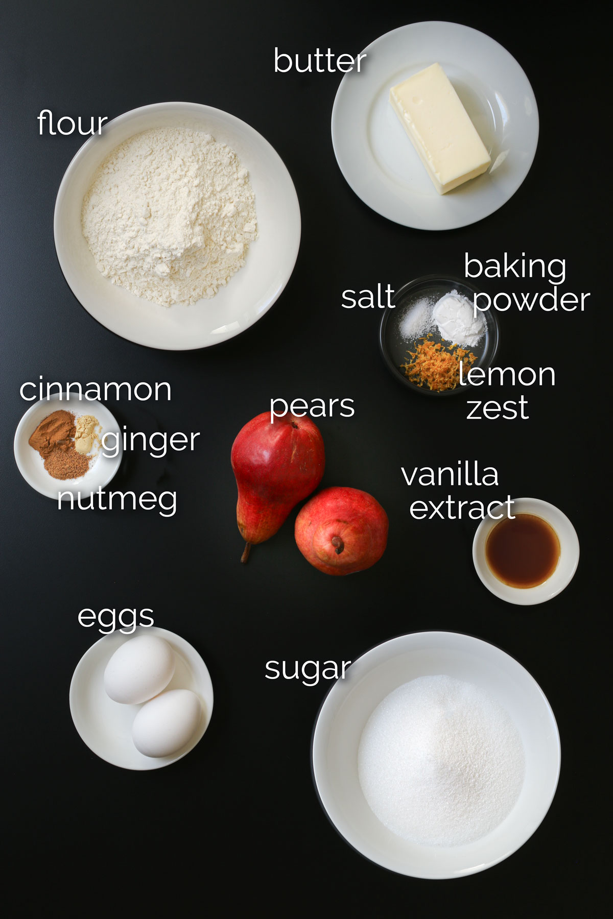 pear cake ingredients laid out on black table top.