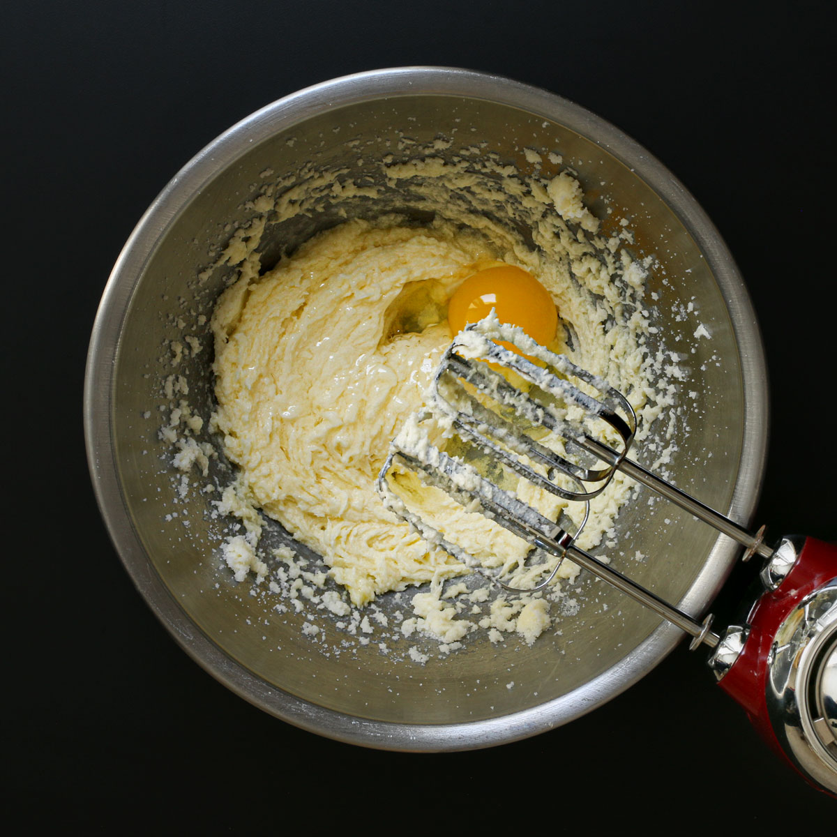 adding egg to butter and sugar mixture in mixing bowl with mixer.