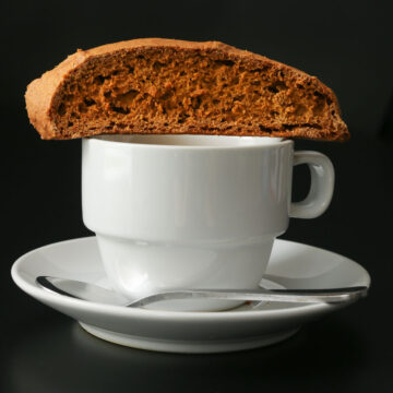 pumpkin biscotti resting on a cup of espresso on saucer with demitasse spoon.