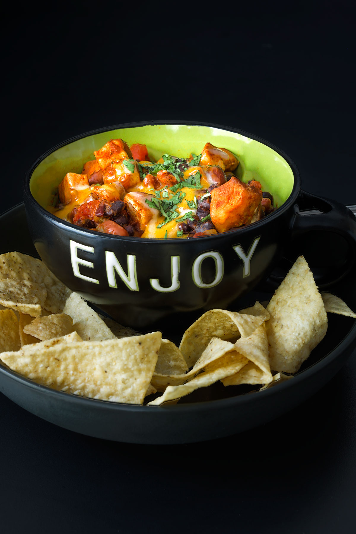 black bowl of chili marked ENJOY on plate of chips on black table top.