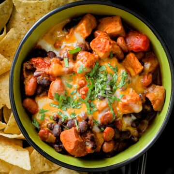 pork chili in a bowl marked ENJOY with a plate of tortilla chips.