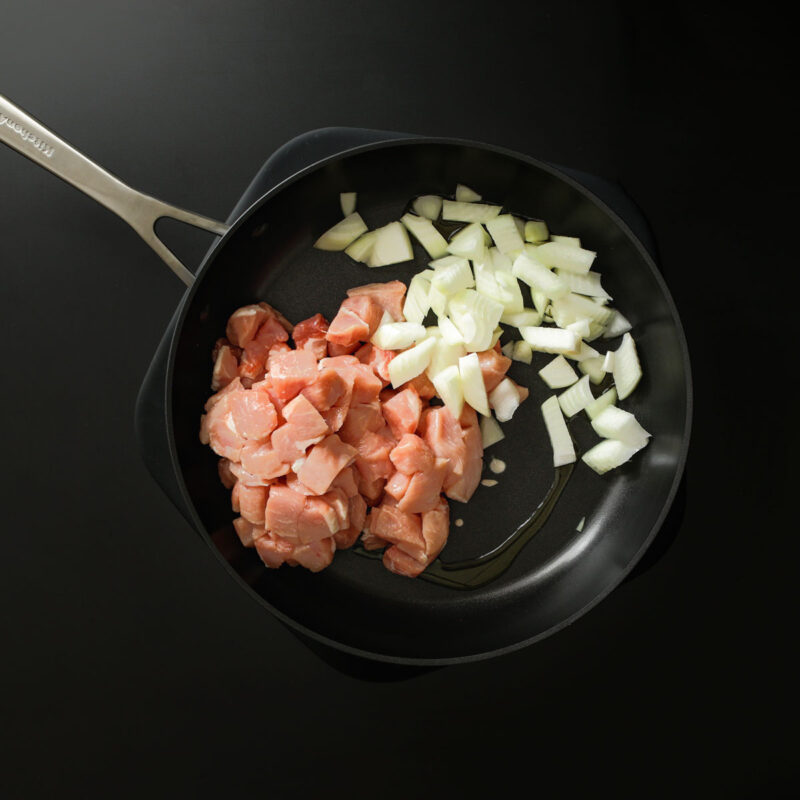 adding pork and onion to a hot skillet.