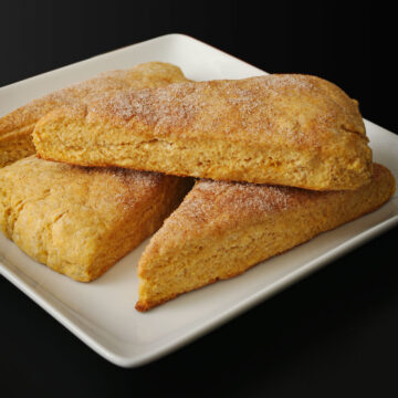 pumpkin scones stacked on white square plate on black table top.