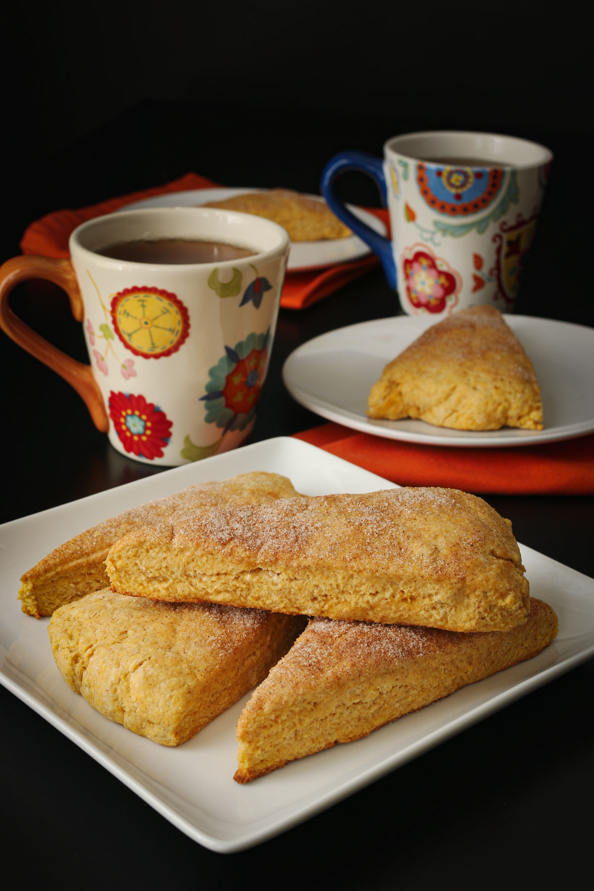 stack of pumpkin scones on square white platter next to cups of coffee.