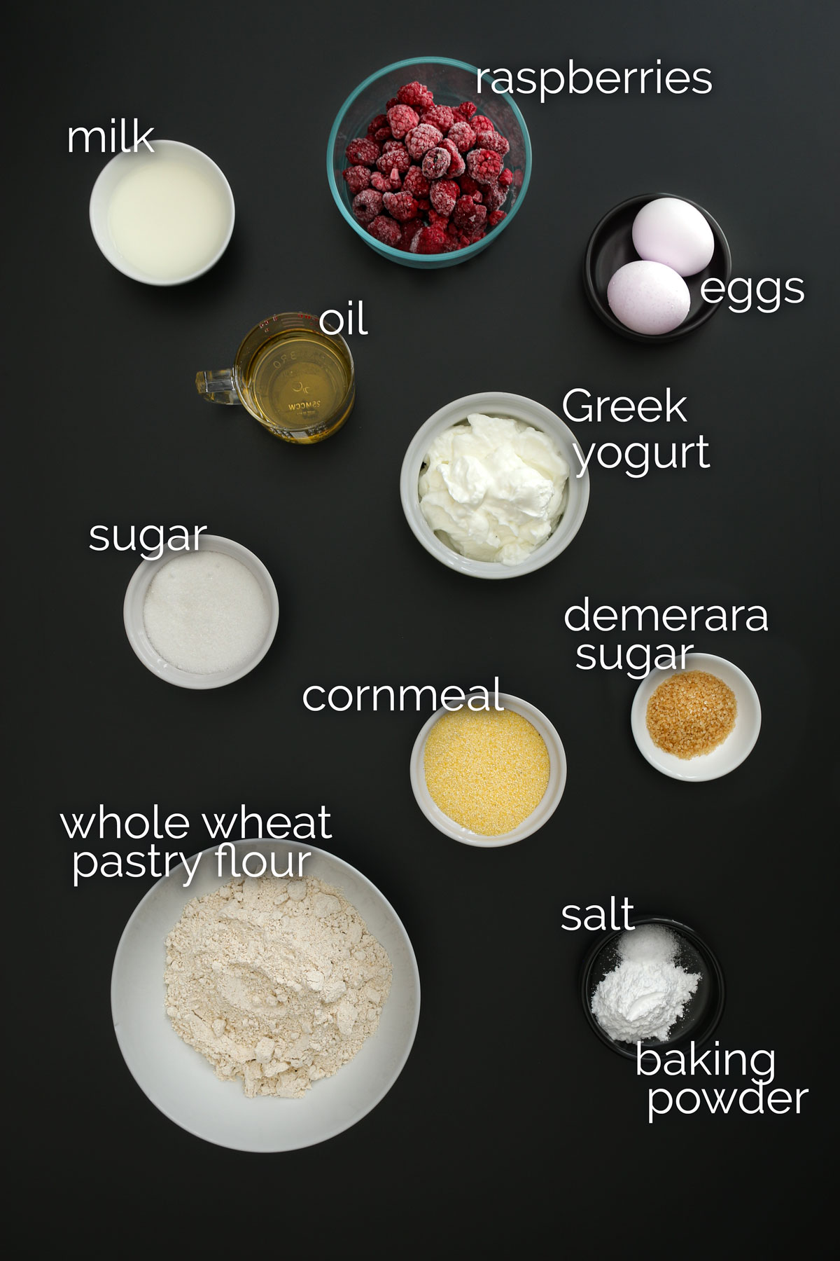ingredients for breakfast cake measured into dishes and laid out on a black table top for an easy mise en place.