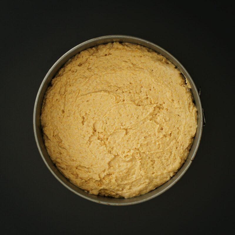 breakfast cake batter spread in prepared springform pan.