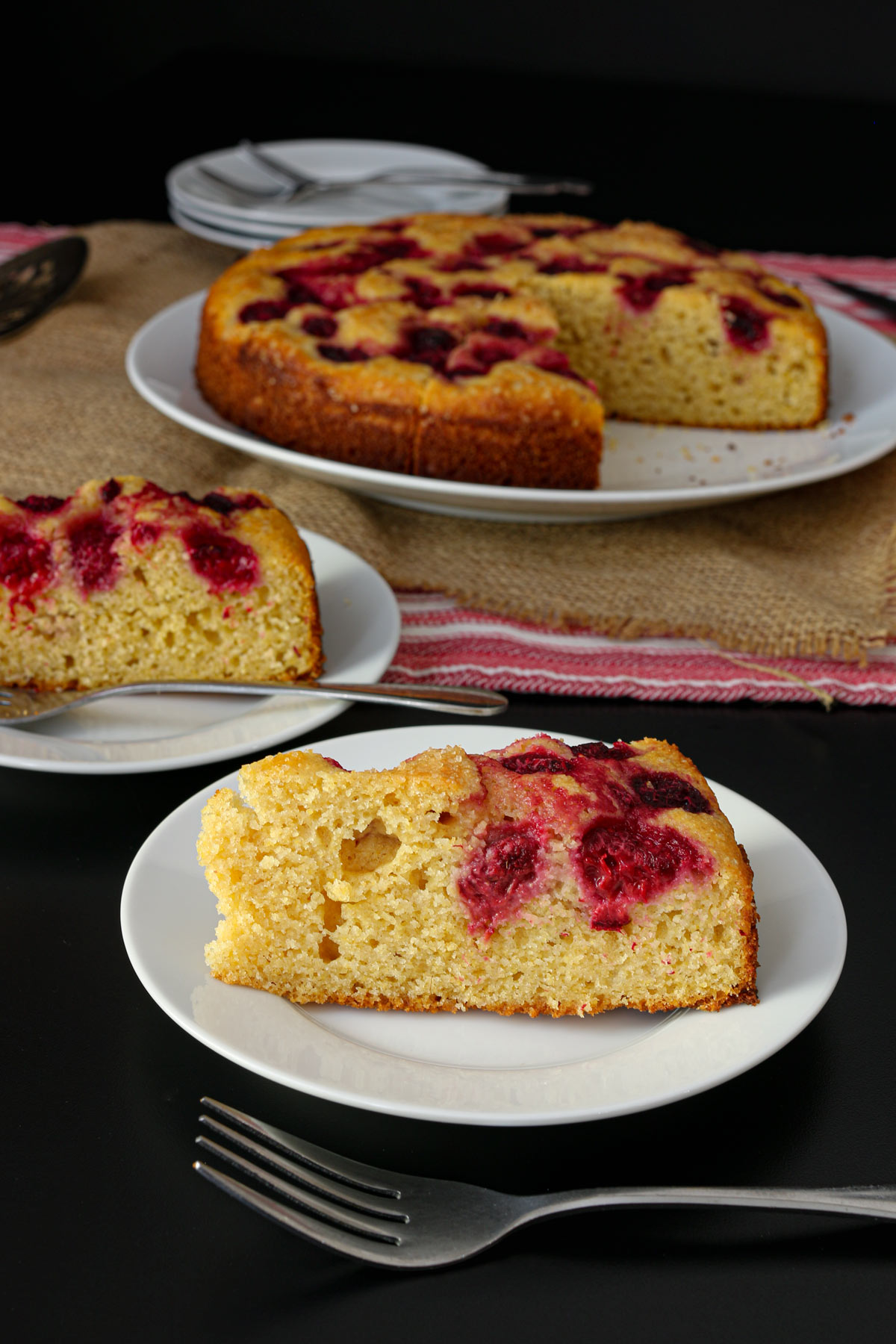 wedges of raspberry breakfast cake dished up on plates with forks next to a platter with the partial cake. A stack of plates and forks are in the background.